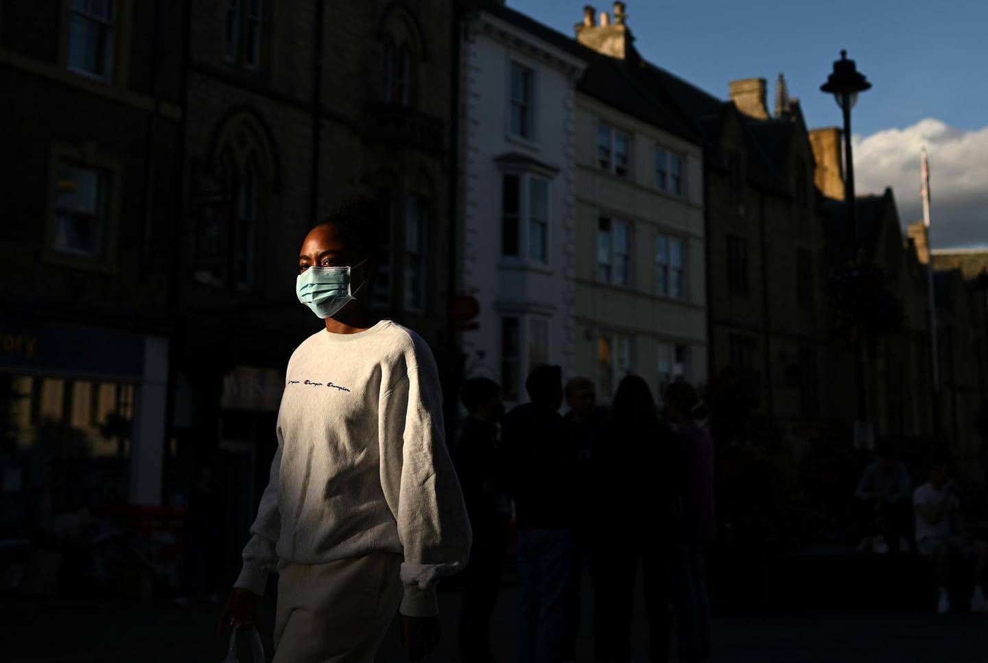 A woman wearing a face mask or covering due to the COVID-19 pandemic, walks in the evening sunshine in Durham, northeast England on September 29, 2020, after tighter restrictions were put in place to help mitigate the spread of COVID-19.  More than two million people in northeast England face new restrictions because of a surge in coronavirus cases, the government announced on Thursday, as it battled to contain a potential second wave of infection. Tighter regulations on socialising are due to come into force from Friday in Northumberland, North and South Tyneside, Newcastle-upon-Tyne, Gateshead, and County Durham. Residents will be banned from socialising in homes or gardens with people from outside their household, while food and drink venues will be restricted to table service only. / AFP / Oli SCARFF