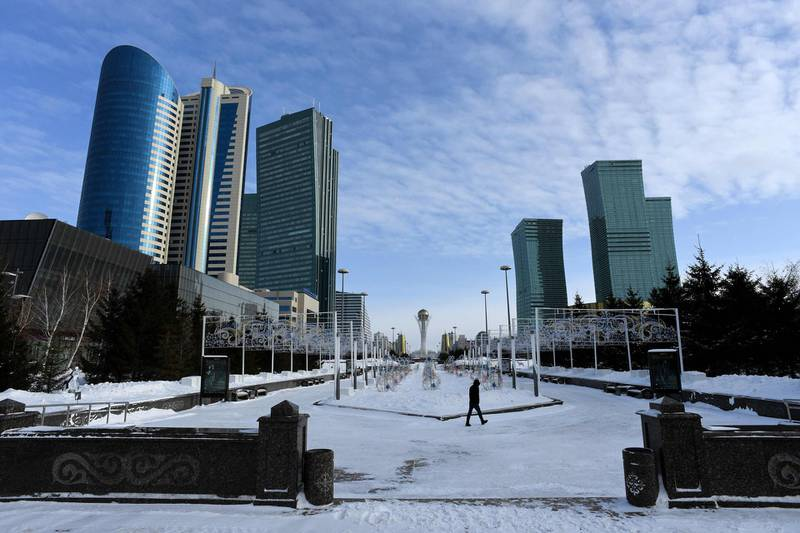 (FILES) In this file photo taken on January 22, 2017 a man walks in downtown Astana, with the Bayterek monument seen in the background. Kazakhstan's parliament on March 20, 2019 voted to rename the country's capital Astana after former president Nursultan Nazarbayev, state media said. / AFP / Kirill KUDRYAVTSEV