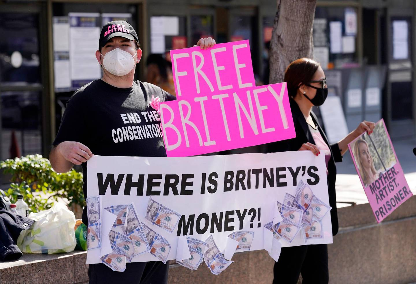 Britney Spears supporters Dustin Strand, left, and Kiki Norberto, both of Phoenix, hold signs outside a court hearing concerning the pop singer's conservatorship at the Stanley Mosk Courthouse, Thursday, Feb. 11, 2021, in Los Angeles. (AP Photo/Chris Pizzello)