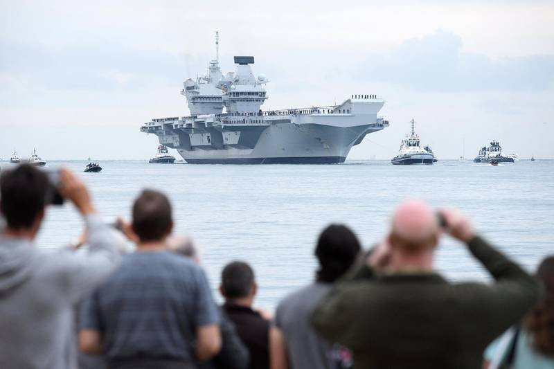 PORTSMOUTH, ENGLAND - AUGUST 16:  Members of the public gather to witness the arrival of the HMS Queen Elizabeth supercarrier as it heads into port on August 16, 2017 in Portsmouth, England.  The HMS Queen Elizabeth is the lead ship in the new Queen Elizabeth class of supercarriers. Weighing in at 65,000 tonnes she is the largest war ship deployed by the British Royal Navy.  (Photo by Leon Neal/Getty Images)