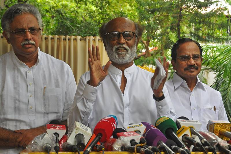 """Indian actor Rajinikanth (C) addresses the media representatives in front of his residence in Chennai on December 3, 2020. Indian film superstar Rajinikanth announced on December 3 that he is going into politics vowing to bring in """"corruption-free"""" politics. / AFP / -"""
