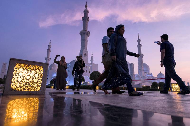 Abu Dhabi, United Arab Emirates, August 31, 2017:    Tourists walk past Sheikh Zayed Grand Mosque as the sun sets ahead of Eid al-Adha in Abu Dhabi on August 31, 2017. Eid al-Adha, or the, Feast of the Sacrifice, honors the willingness of Ibrahim to sacrifice his son Ismaeel, as an act of obedience to God's command. Christopher Pike / The National  Reporter:  N/A Section: News