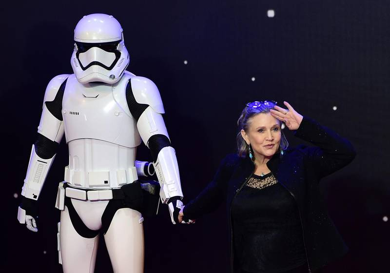 """(FILES) In this file photo taken on December 16, 2015 US actress Carrie Fisher (R) poses with a storm trooper as she attends the opening of the European Premiere of """"Star Wars: The Force Awakens"""" in central London. July 27, 2018,""""Star Wars: Episode IX"""" begins filming next week, Disney said Friday, in a shock announcement revealing it will feature both Carrie Fisher in a posthumous appearance and series star Mark Hamill. / AFP / LEON NEAL / TO GO WITH AFP STORY BY FRANKIE TAGGART"""