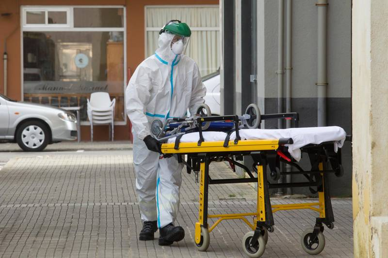 A health staff team member wearing a protective suit to protect against coronavirus enters a home in A Marina, near Lugo, northwest Spain, Sunday, July 5, 2020. Authorities in northwestern Spain have ordered the lockdown of a county with a population of 71,000 for fears of a coronavirus outbreak. Regional authorities in Galicia announced Sunday that movement to and from A Marina county located on Spain's northern Atlantic coast will be prohibited starting at midnight and will run through Friday. (Carlos Castro/Europa Press via AP)