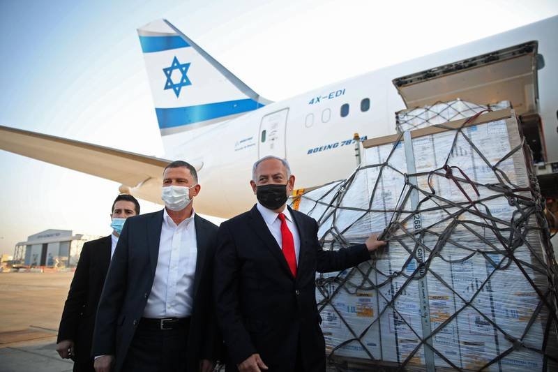 Israel's Prime Minister Benjamin Netanyahu (R) and Health Minister Yuli Edelstein (C) attend a ceremony for the arrival of a plane carrying a shipment of Pfizer-BioNTech anti-coronavirus vaccine, at Ben Gurion airport near the Israeli city of Tel Aviv on January 10, 2021. Netanyahu announced earlier this week that he had signed a deal for enough doses of the Pfizer-BioNTech vaccine for all Israelis over 16 to be innoculated. Israel, with a population of nine million, has recorded over 3,600 deaths from the Covid-19 illness.  / AFP / POOL / Motti MILLROD