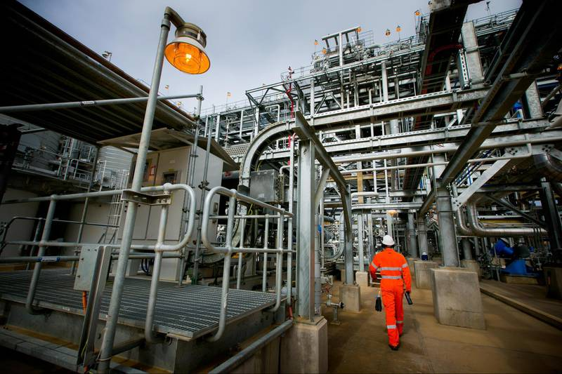 A worker walks through the Curtis Island liquefied natural gas (LNG) plant, a part of the Queensland Curtis Liquefied Natural Gas (QCLNG) project site operated by QGC Pty, a unit of Royal Dutch Shell Plc, in Gladstone, Australia, on Wednesday, June 15, 2016. Gas from more than 2,500 wells travels hundreds of miles by pipeline to the project, where it's chilled and pumped into 10-story-high tanks before being loaded onto massive ships. Photographer: Patrick Hamilton/Bloomberg