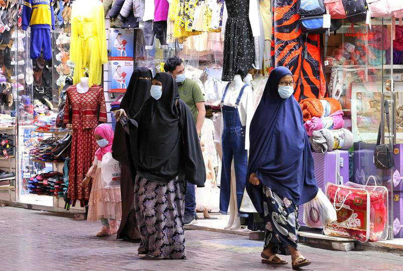 Shoppers walk outside stores in Dubai on May 5, 2021 after it opened following the breaking of the fast during the Muslim holy fasting month of Ramadan.  / AFP / Karim SAHIB