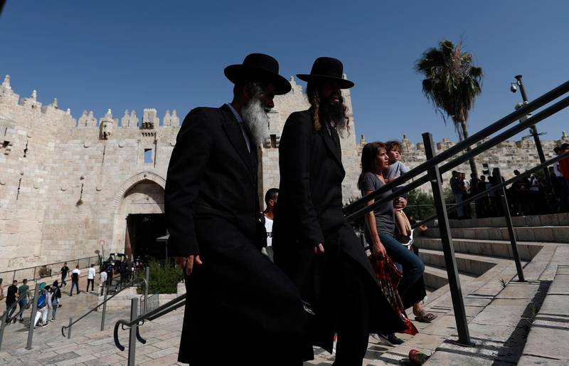 epa09260484 Ultra-Orthodox men walk by at Damascus gate during the visit of Israeli far-right member of (Otzma Yehudit) party and the Knesset (parliament) Itamar Ben-Gvir, to  Damascus gate of Jerusalem's old city, on 10 June 2021.  EPA/ATEF SAFADI