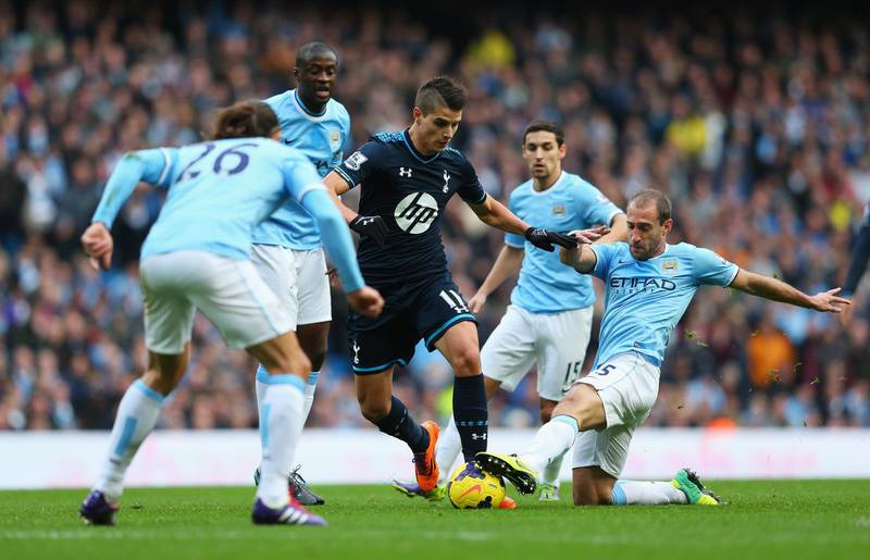MANCHESTER, ENGLAND - NOVEMBER 24: Erik Lamela of Tottenham Hotspur is tackled by Pablo Zabaleta of Manchester City during the Barclays Premier League match between Manchester City and Tottenham Hotspur at Etihad Stadium on November 24, 2013 in Manchester, England.  (Photo by Alex Livesey/Getty Images)