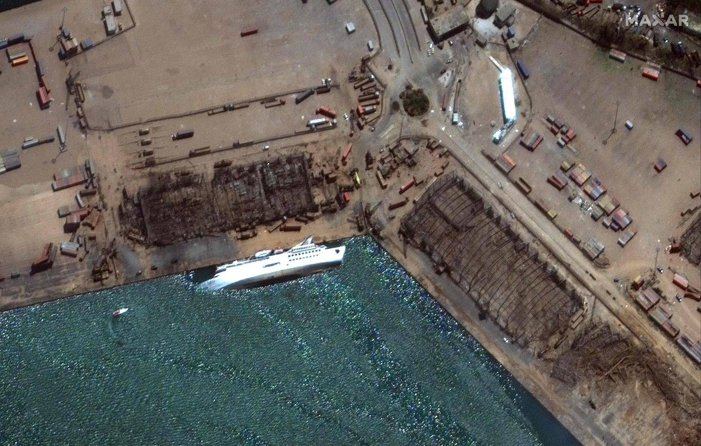 """This August 5, 2020, handout satellite image obtained courtesy of  Maxar Technologies shows the capsized Orient Queen cruise ship after the explosion in Beirut on August 4, 2020. For at least six years, hundreds of tonnes of ammonium nitrate, which Lebanese authorities say caused Tuesday's massive blast, were negligently stored in a Beirut port warehouse, waiting for disaster to strike. The odourless crystalline substance commonly used as a fertiliser has caused numerous industrial explosions over the decades -- including the massive one in Beirut that killed at least 113 people, wounded thousands and left 300,000 homeless - RESTRICTED TO EDITORIAL USE - MANDATORY CREDIT """"AFP PHOTO / Satellite image ©2020 Maxar Technologies """" - NO MARKETING - NO ADVERTISING CAMPAIGNS - DISTRIBUTED AS A SERVICE TO CLIENTS  / AFP / Satellite image ©2020 Maxar Technologies / Handout / RESTRICTED TO EDITORIAL USE - MANDATORY CREDIT """"AFP PHOTO / Satellite image ©2020 Maxar Technologies """" - NO MARKETING - NO ADVERTISING CAMPAIGNS - DISTRIBUTED AS A SERVICE TO CLIENTS"""