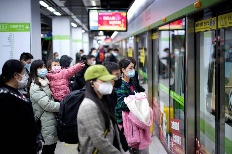 People wearing face masks wait for a subway train on the first day the city's subway services resumed following the novel coronavirus disease (COVID-19) outbreak, in Wuhan of Hubei province, the epicentre of China's coronavirus outbreak, March 28, 2020. The Chinese characters  REUTERS/Aly Song