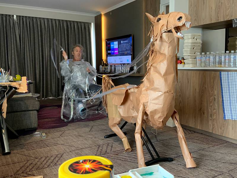 David Marriott poses with his paper horse in his hotel room in Brisbane, Australia, April 6, 2021. While in quarantine inside his Brisbane hotel room, art director Russell Brown was bored and started making a cowboy outfit from the paper bags his meals were being delivered in. His project expanded to include a horse and a clingfilm villain that he has daily adventures with, in images that have gained a huge online following. (David Marriott via AP)