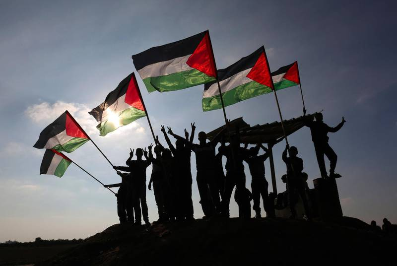 TOPSHOT - Palestinian protesters wave their national flag near the Israel-Gaza border east of the southern Gaza Strip city of Khan Yunis as they demonstrate against calls for the closure of UNRWA by the Israeli prime minister and cuts in Palestinian aid by the American president on January 9, 2018. / AFP PHOTO / SAID KHATIB