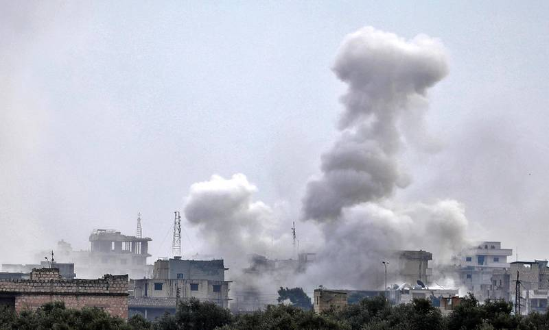 This picture taken on February 4, 2020 shows smoke plumes billowing from bombardment by the Syrian government forces and allies on the town of Sarmin, southeast of the city of Idlib in the northwestern province of the same name. (Photo by Omar HAJ KADOUR / AFP)