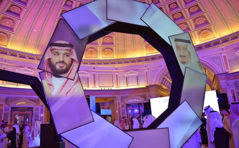 Pictures of Saudi Crown Prince Mohammad Bin Salman (L) and King Salman (R) are displayed during the first session of Saudi Arabia's National Industrial Development and Logistics Program (NIDLP) at the Ritz Carlton in Riyadh on January 28, 2019. / AFP / FAYEZ NURELDINE