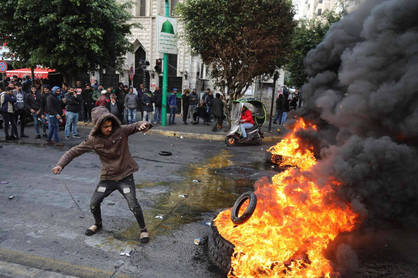 TOPSHOT - A protester throws a tyre on a burning pile blocking the road in the capital Beirut on January 22, 2020. Lebanon ended a painful wait by unveiling a new cabinet line-up, but the government was promptly scorned by protesters and faces the Herculean task of saving a collapsing economy. / AFP / IBRAHIM AMRO