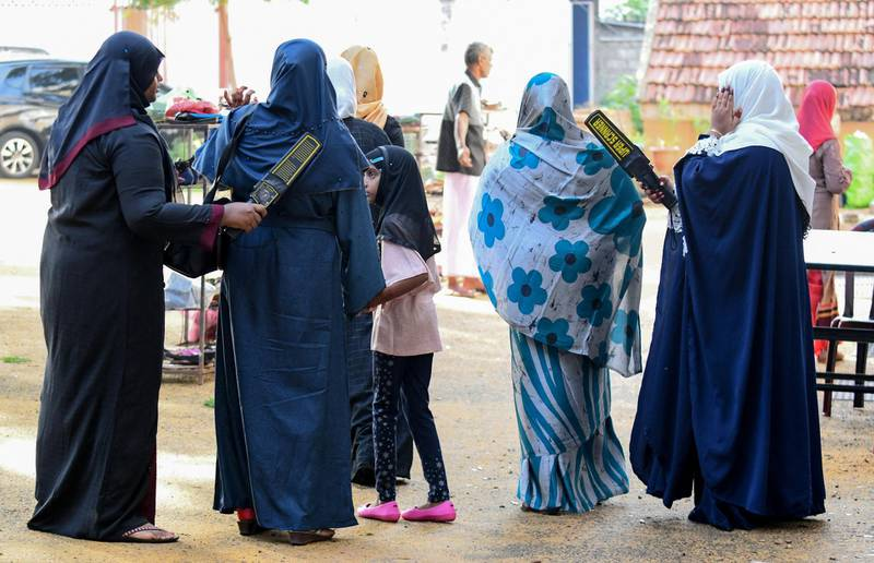 Sri Lankan Muslim women search devotees at the entrance of the Grand Mosque on the first day of Eid al-Fitr in Colombo on July 5, 2019. - Muslims around the world are celebrating the Eid al-Fitr festival, which marks the end of the fasting month of Ramadan. (Photo by LAKRUWAN WANNIARACHCHI / AFP)