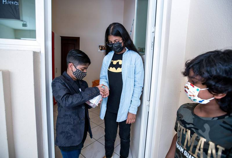 Ayaan Tariq, 7, sanitizes his friends hands, Ayesha, 10, before lending her books from his library on June 22, 2021.  Victor Besa / The National.Reporter: Anam Rizi for News