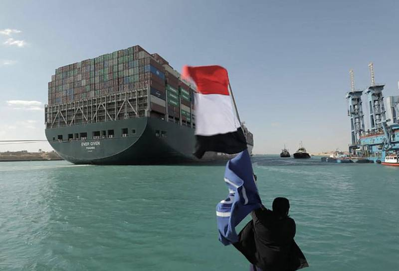 """A picture released by Egypt's Suez Canal Authority on March 29, 2021, shows a man waving the Egyptian flag after Panama-flagged MV 'Ever Given' container ship was fully dislodged from the banks of the Suez. The ship was refloated and the Suez Canal reopened, sparking relief almost a week after the huge container ship got stuck and blocked a major artery for global trade. Salvage crews have been working around the clock ever since the accident which has been blamed on high winds and poor visibility during a sandstorm. / AFP / SUEZ CANAL AUTHORITY / - / == RESTRICTED TO EDITORIAL USE - MANDATORY CREDIT """"AFP PHOTO / HO / SUEZ CANAL AUTHORITY"""" - NO MARKETING NO ADVERTISING CAMPAIGNS - DISTRIBUTED AS A SERVICE TO CLIENTS =="""