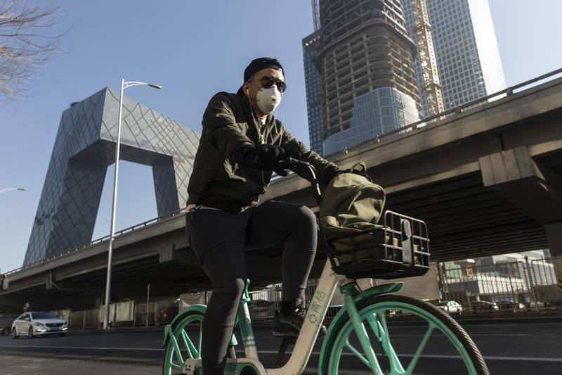 A cyclist wearing a protective mask ridies near the CCTV building, left, in Beijing, China, on Tuesday, March 17, 2020. China suffered an even deeper slump than analysts feared at the start of the year as the coronavirus shuttered factories, shops and restaurants across the nation, underscoring the fallout now facing the global economy as the virus spreads around the world. Photographer: Qilai Shen/Bloomberg