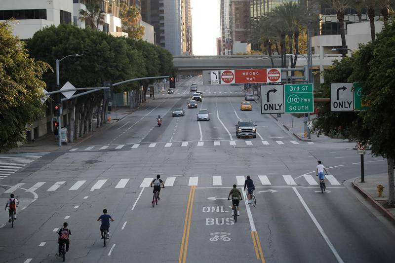 A group of cyclists take advantage of the light traffic along Figueroa Street on Wednesday, April 1, 2020, in Los Angeles. The spread of the coronavirus statewide has, so far, been slow enough to give the state time to prepare for an expected spike in cases. (AP Photo/Marcio Jose Sanchez)