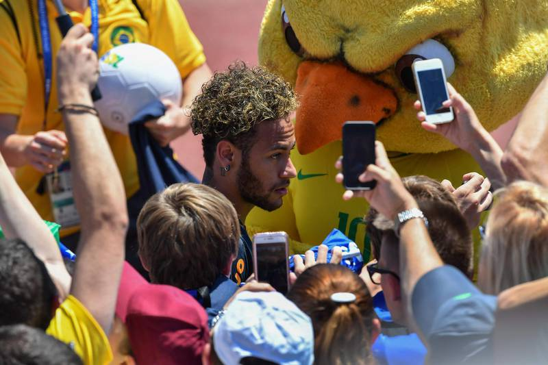 Fans take photographs of Brazil's Neymar after a training session at Sochi Municipal Stadium in Sochi on June 12, 2018, ahead of the Russia 2018 World Cup football tournament. / AFP / Nelson ALMEIDA