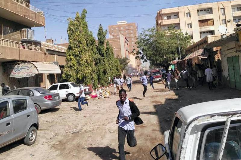 """Sudanese protesters run away from tear gas smokes during a demonstration in Khartoum, on December 31, 2018. - Police fired tear gas at protesters in Sudan's capital on December 31 ahead of a planned march on President Omar al-Bashir's palace calling on him to """"step down"""" following deadly anti-government protests. (Photo by - / AFP)"""