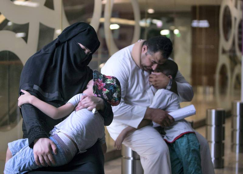 DUBAI, UNITED ARAB EMIRATES, MARCH 30, 2018 - Alruwayda, with her son Abdul Hadi and her husband Mahmoud Nimr in the background with her other son Rahed. The family is asking for donations to help pay for rent and expenses in Deira, Dubai. (Leslie Pableo for The National)