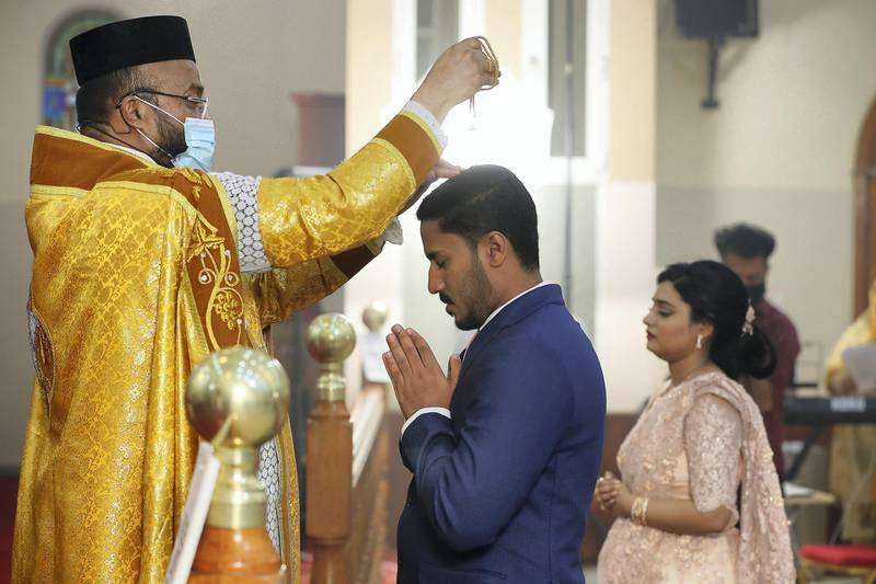 DUBAI, UNITED ARAB EMIRATES , October 26– 2020 :- Father performing marriage prayer and wearing protective face mask as a preventive measure against the spread of coronavirus during the marriage ceremony of Justin George (groom) and Jubee Vargheese (bride) held at the St. Thomas Orthodox Cathedral in Dubai. Relatives and friends wearing protective face mask and gloves as a preventive measure against the spread of coronavirus and maintaining social distance during the ceremony. (Pawan Singh / The National) For News/Online/Instagram. Story by Kelly