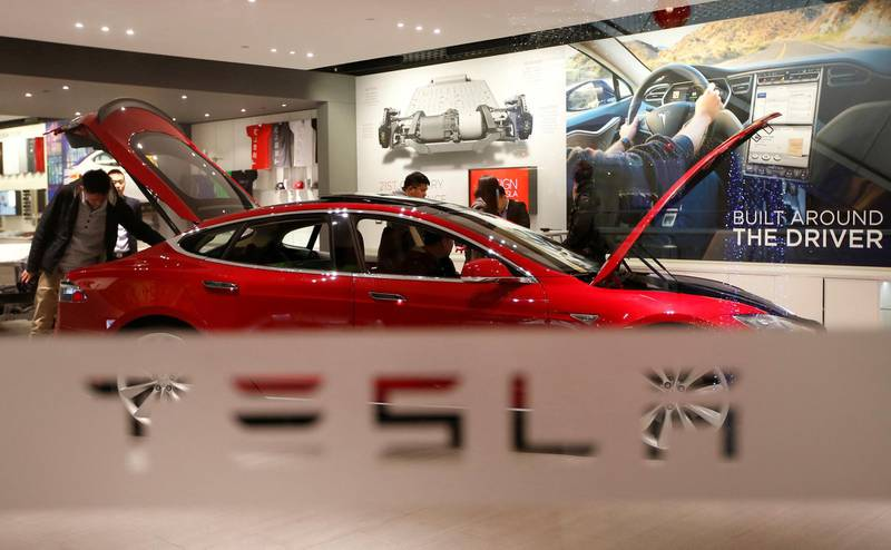 FILE PHOTO: A man looks at a Tesla Model S car at its showroom in Beijing, China January 29, 2014. REUTERS/Kim Kyung-Hoon/File Photo