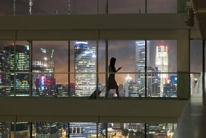 Young woman using smartphone and pulling suitcase, city skyline in view. Getty Images