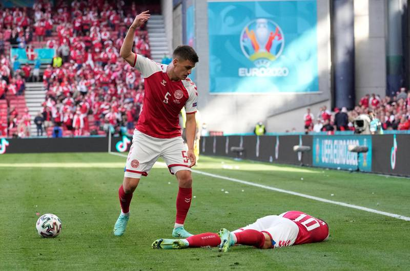 FILE - In this file photo dated Saturday, June 12, 2021, Denmark's Joakim Maehle reacts as Denmark's Christian Eriksen lies on the pitch after collapsing during the Euro 2020 soccer championship group B match against Finland at Parken stadium in Copenhagen.  Christian Eriksen has been discharged from the hospital nearly a week after collapsing on the field during a Euro 2020 soccer match, according to a statement from Danish soccer federation Friday June 18, 2021. (AP Photo/Martin Meissner, FILE)