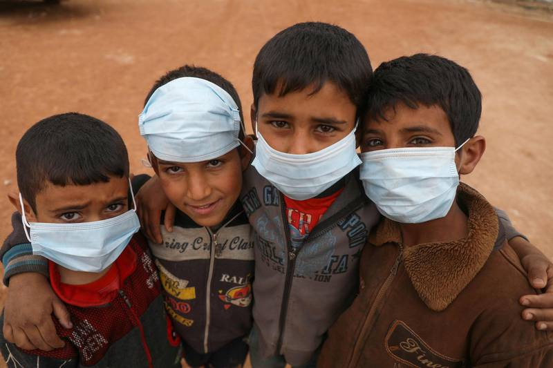 Syrian boys pose for a picture during an awareness workshop on Coronavirus (COVID-19) held by Doctor Ali Ghazal at a camp for displaced people in Atme town in Syria's northwestern Idlib province, near the border with Turkey, on March 14, 2020. (Photo by AAREF WATAD / AFP)