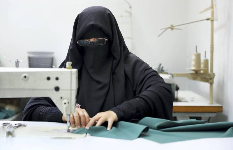 DUBAI , UNITED ARAB EMIRATES , NOV 1   – 2017  :- Aisha Abdul Qader Saeed stitching Dubai Police officers uniform in the tailoring section at the Dubai Police Headquarter in Dubai. She lost her hearing and speech when she was a child.  (Pawan Singh / The National) Story by Nawal Al Ramahi