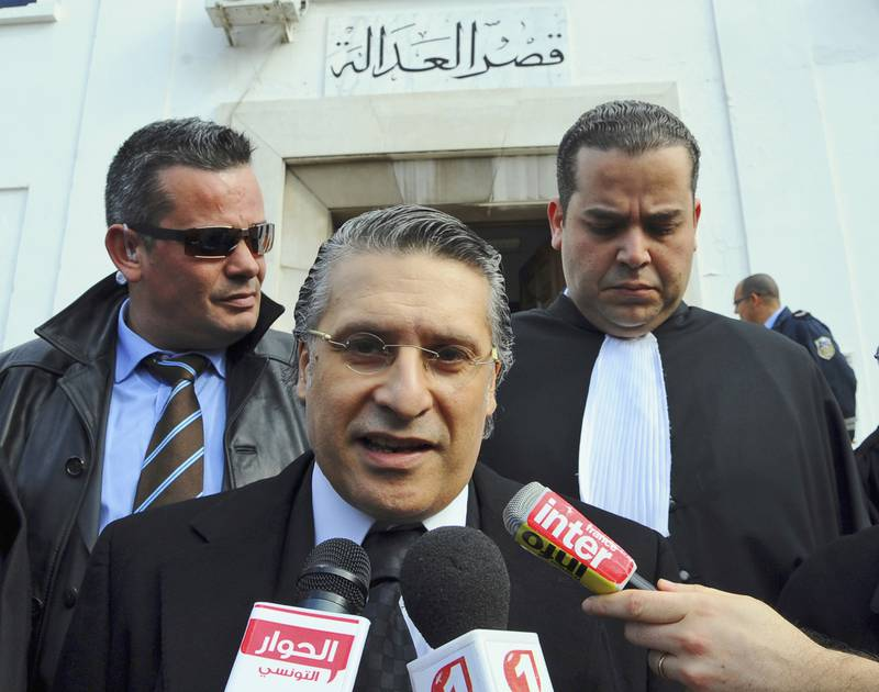 FILE - In this Jan.23 2012 file photo, the owner of the Tunisian private channel Nessma TV, Nabil Karoui, center, leaves the Tunis courthouse after attending his trial. A leading presidential candidate in Tunisia, Nabil Karoui, co-owner of a private TV station, has been arrested and jailed in a case involving alleged tax evasion and money laundering. (AP Photo/Hassene Dridi, File)