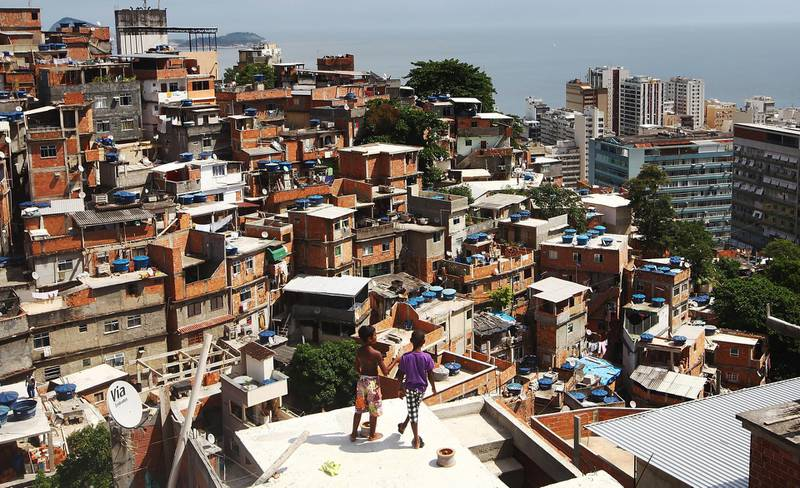 RIO DE JANEIRO, BRAZIL - FEBRUARY 21:  Boys gather while flying kites in the Cantagalo shantytown community next to neighboring Pavao-Pavaozinho on February 21, 2014 in Rio de Janeiro, Brazil. The pacified favelas stand above Copacabana and Ipanema beaches. Ahead of the World Cup, some of Rio's pacified favelas have seen an increase in violence, including a number of shootings in Cantagalo and Pavao-Pavaozinho. Around 10,000 people live in the Cantagalo and Pavao-Pavaozinho communities with a total of 1.7 million Rio residents residing in shantytowns, many of which are controlled by drug traffickers.  (Photo by Mario Tama/Getty Images)