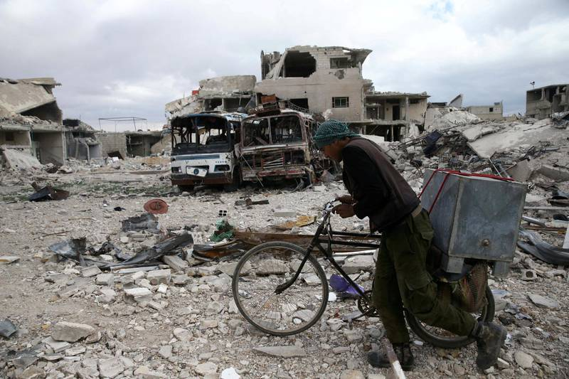 A man walks with his bicycle at a damaged site in the besieged town of Douma, Eastern Ghouta, in Damascus, Syria March 30, 2018. REUTERS/Bassam Khabieh     TPX IMAGES OF THE DAY