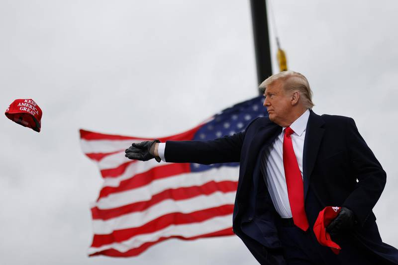 """U.S. President Donald Trump tosses out """"Make America Great Again"""" (MAGA) caps as he arrives for a campaign rally at Oakland County International Airport in Waterford Township, Michigan, U.S., October 30, 2020. REUTERS/Carlos Barria"""