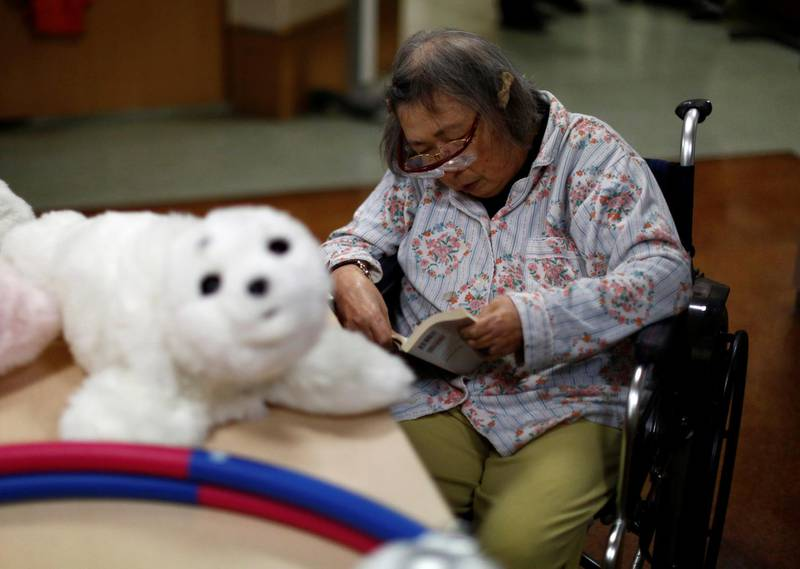 """A resident reads a book during a session with 'AIBO'a pet dog robot and 'PARO' a robot seal at Shin-tomi nursing home in Tokyo, Japan, February 2, 2018. REUTERS/Kim Kyung-Hoon  SEARCH """"KYUNG-HOON ROBOTS"""" FOR THIS STORY. SEARCH """"WIDER IMAGE"""" FOR ALL STORIES."""