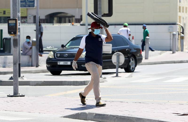 DUBAI, UNITED ARAB EMIRATES , May 6 – 2020 :- A person wearing protective face mask and covering his face with laptop bag on a hot day in Bur Dubai area in Dubai. UAE government ease the coronavirus restriction for the residents around the country. (Pawan Singh / The National) For News/Standalone/Online/Stock/Instagram
