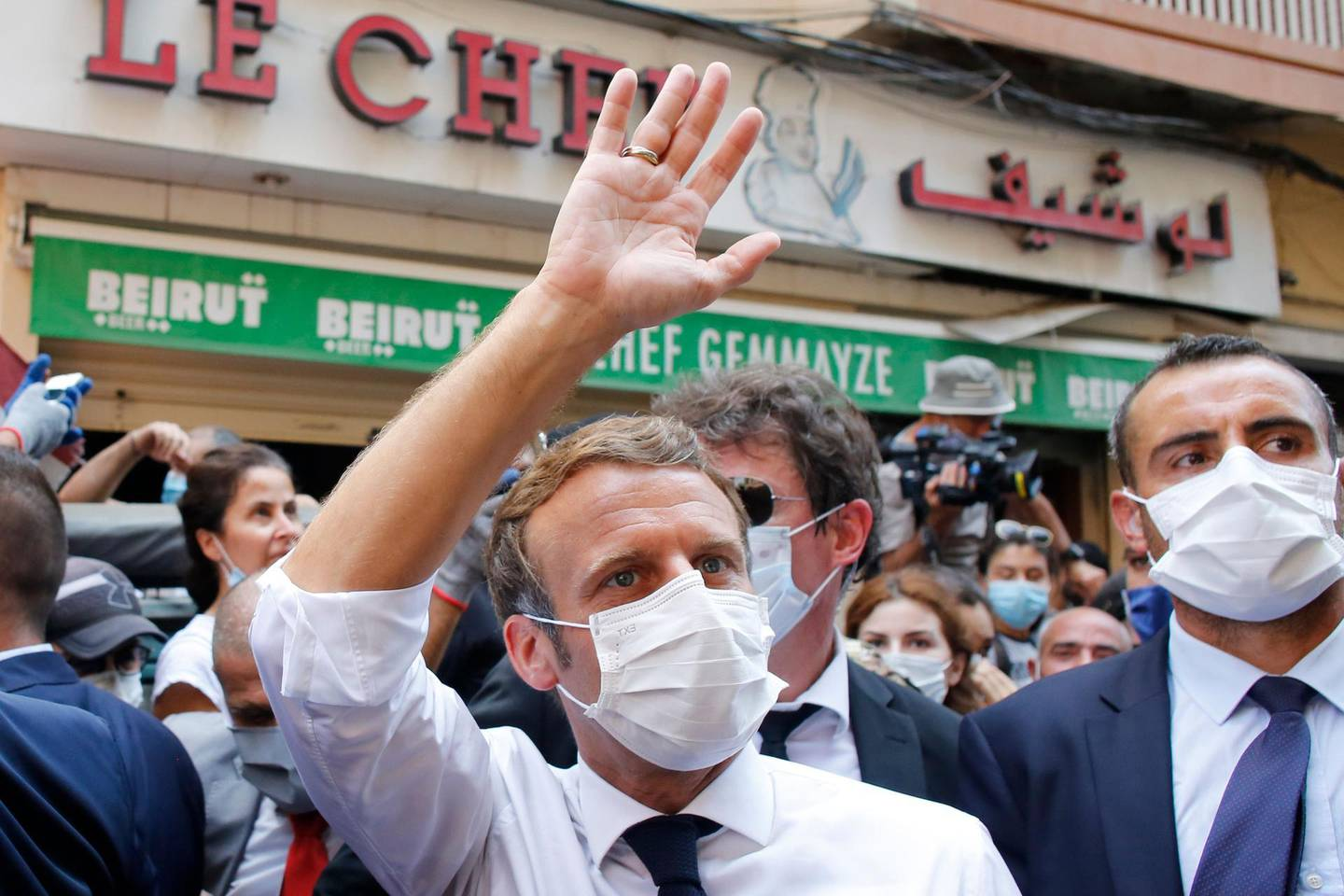 (FILES) In this file photo taken on August 06, 2020, French President Emmanuel Macron (C) waves in front of Beirut's landmark traditional restaurant Le Chef during his tour of the Lebanese capital's heavily-damaged Gemmayzeh neighbourhood on August 6, 2020, two days after a the massive port explosion which devastated the city in a disaster that has sparked grief and fury across the world.  Hollywood star Russell Crowe said on August 13, 2020 that he donated funds to help rebuild a blast-hit Beirut restaurant on behalf of late food icon Anthony Bourdain, who loved its traditional dishes. The decades-old Le Chef restaurant, located in the heart of a trendy Beirut district, is a beloved neighbourhood place renowned for its home-style cooking.  / AFP / POOL / Thibault Camus