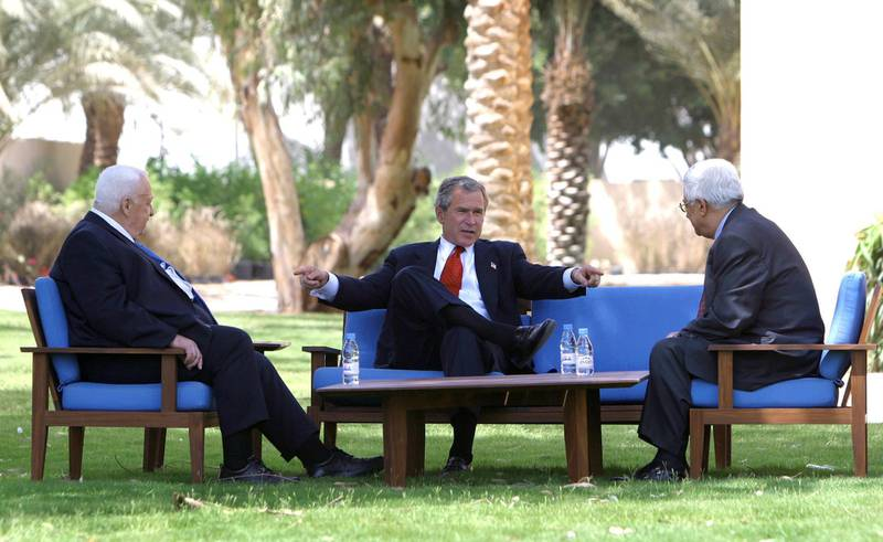 U.S. President George W. Bush discusses the Middle East peace process with Prime Minister Ariel Sharon of Israel (L) and Palestinian Prime Minister Mahmoud Abbas (R) in Aqaba, Jordan, June 4, 2003. REUTERS/Paul Morse/White House  HK/ME