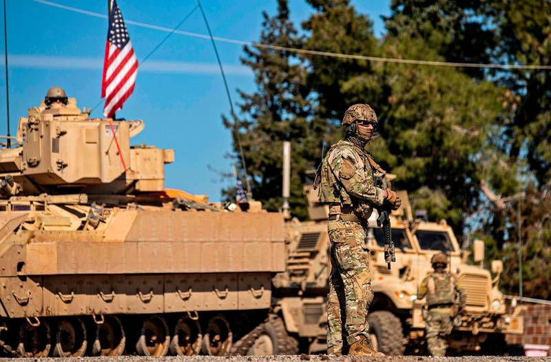 A US soldier stands by a Bradley Fighting Vehicle (BFV) during a patrol in the countryside near al-Malikiyah (Derik) in Syria's northeastern Hasakah province on February 2, 2021.  / AFP / Delil SOULEIMAN