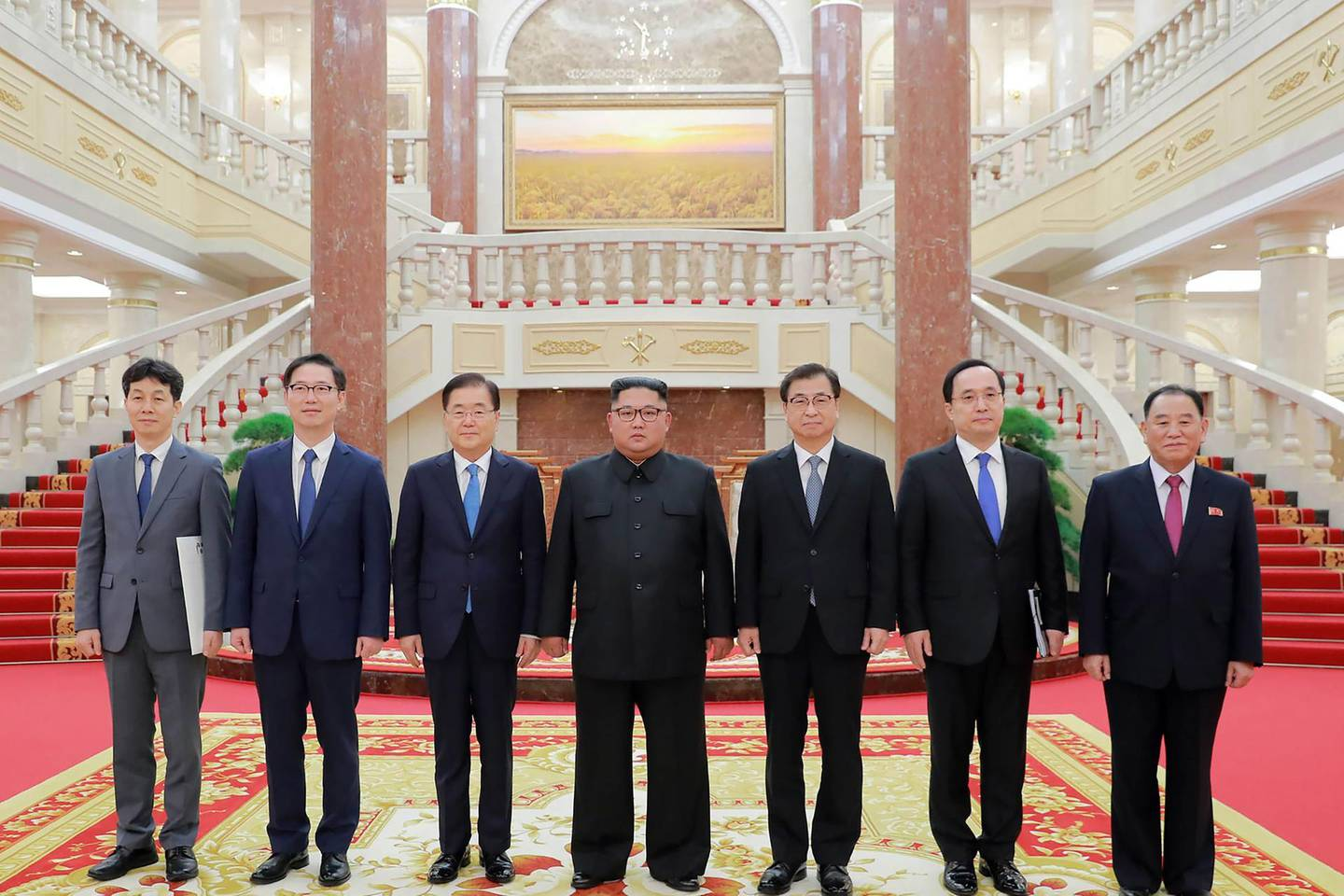 """This picture from North Korea's official Korean Central News Agency (KCNA) taken on September 5, 2018 and released on September 6, 2018 shows North Korean leader Kim Jong Un (C) posing for a picture with a delegation of South Korean president's special envoy, led by Chung Eui-yong (3rd L), in Pyongyang. - Kim Jong Un will meet the South's President Moon Jae-in at a summit in Pyongyang in September to discuss the nuclear disarmament, Seoul said on September 6. (Photo by KCNA VIA KNS / KCNA VIA KNS / AFP) / South Korea OUT / REPUBLIC OF KOREA OUT   ---EDITORS NOTE--- RESTRICTED TO EDITORIAL USE - MANDATORY CREDIT """"AFP PHOTO/KCNA VIA KNS"""" - NO MARKETING NO ADVERTISING CAMPAIGNS - DISTRIBUTED AS A SERVICE TO CLIENTS THIS PICTURE WAS MADE AVAILABLE BY A THIRD PARTY. AFP CAN NOT INDEPENDENTLY VERIFY THE AUTHENTICITY, LOCATION, DATE AND CONTENT OF THIS IMAGE. THIS PHOTO IS DISTRIBUTED EXACTLY AS RECEIVED BY AFP. /"""