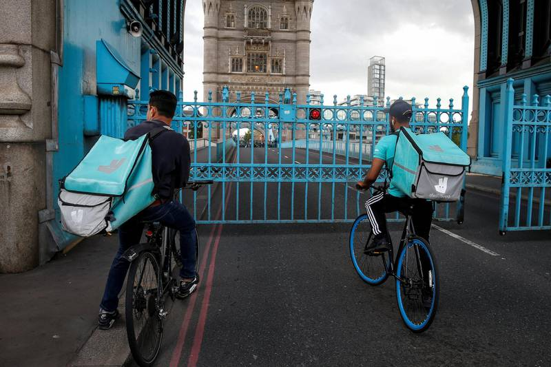 LONDON, ENGLAND - AUGUST 22: Deliveroo riders stuck on Tower Bridge on August 22, 2020 in London, England. Tower Bridge was closed this afternoon to due a mechanical fault. The bridge was reopened to pedestrians and cyclists just after 5:45pm. (Photo by Hollie Adams/Getty Images)