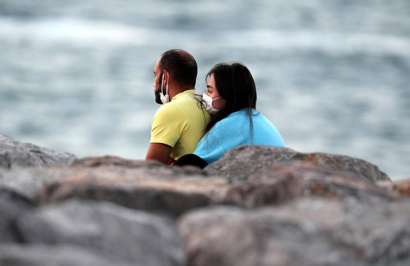 DUBAI, UNITED ARAB EMIRATES , December 31 – 2020 :- Couple watching the last sunset of 2020 from the Palm Jumeirah in Dubai. ( Pawan Singh / The National ) For News/Standalone/Online/Instagram/Big Picture