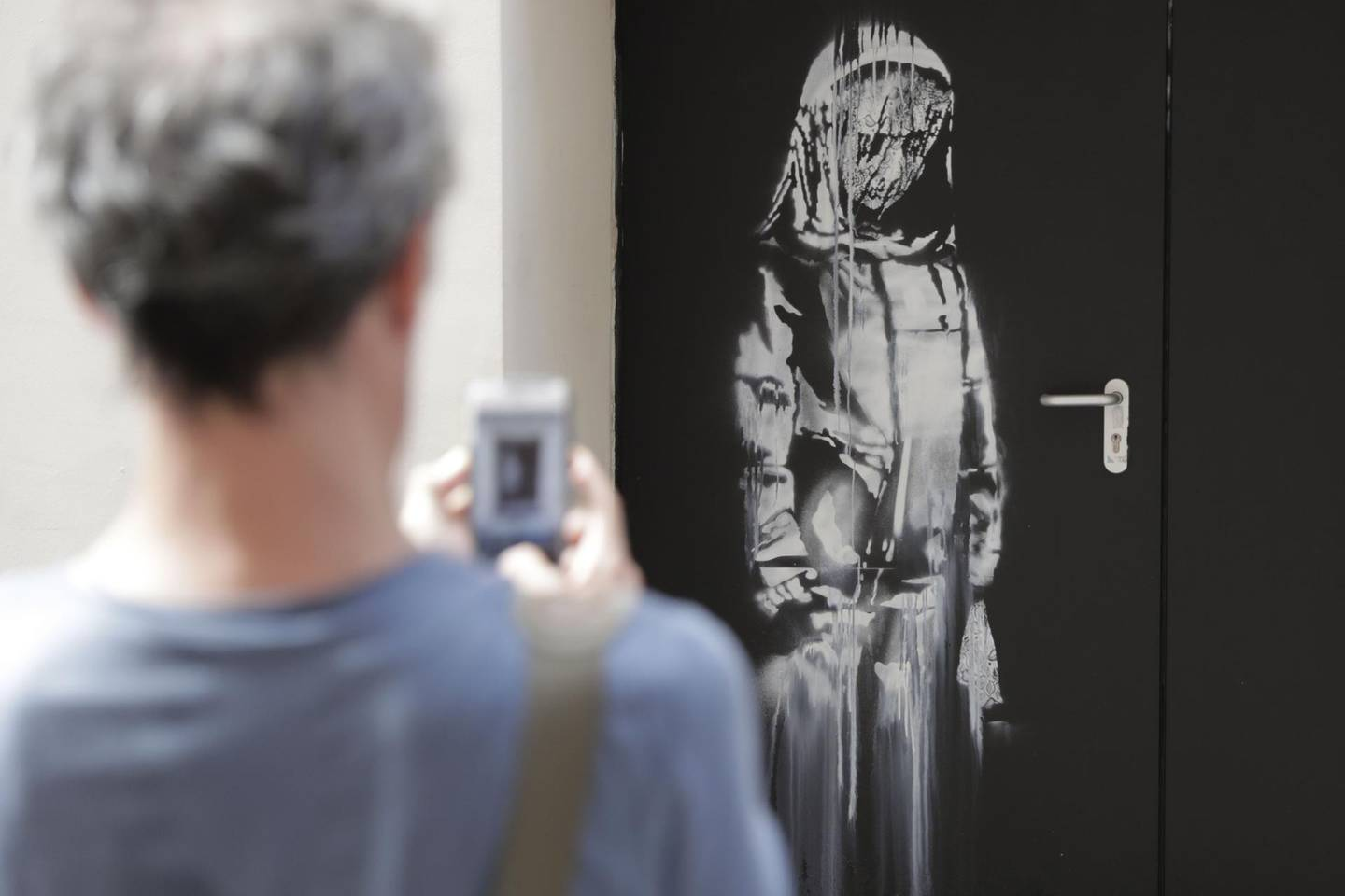 (FILES) In this file photo taken on June 25, 2018 a man takes a photograph of an artwork by street artist Banksy in Paris on a side street to the Bataclan concert hall where a terrorist attack killed 90 people on Novembre 13, 2015. The stolen Banksy work has been found in Italy, AFP reports on June 10, 2020.  - RESTRICTED TO EDITORIAL USE - MANDATORY MENTION OF THE ARTIST UPON PUBLICATION - TO ILLUSTRATE THE EVENT AS SPECIFIED IN THE CAPTION  / AFP / Thomas SAMSON / RESTRICTED TO EDITORIAL USE - MANDATORY MENTION OF THE ARTIST UPON PUBLICATION - TO ILLUSTRATE THE EVENT AS SPECIFIED IN THE CAPTION