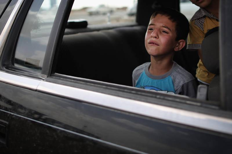 KALAK, IRAQ - JUNE 13:  A boy cries for reasons unknown while waiting in a car at a Kurdish checkpoint on June 13, 2014 in Kalak, Iraq. Thousands of people have fled Iraq's second city of Mosul after it was overrun by ISIS (Islamic State of Iraq and Syria) militants. Many have been temporarily housed at various IDP (internally displaced persons) camps around the region including the area close to Erbil, as they hope to enter the safety of the nearby Kurdish region.  (Photo by Dan Kitwood/Getty Images)