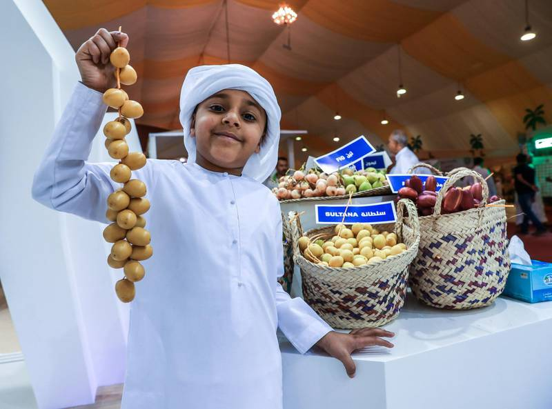 Abu Dhabi, U.A.E., July 18, 2018.  First day of the 2018 Liwa Date Festival. --  Jasim Al Qemzi (7)poses for a souvenir photo with some Sultana dates from Zirku Island.Victor Besa / The NationalSection:  NAReporter:  Haneen Dajani