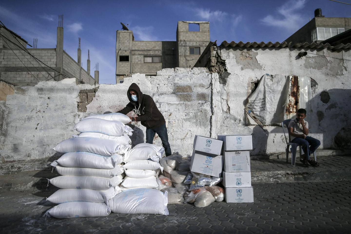 A Palestinian man wearing a protective mask sorts food aid provided by the United Nations Relief and Works Agency for Palestinian Refugees (UNRWA), to be delivered to refugee homes at the al-Shati camp, in Gaza city, on April 6, 2020, instead of the usual distribution at a UN center in the city, due to the COVID-19 pandemic. / AFP / MOHAMMED ABED